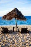 Sunbed and nipa sun umbrella on the white sand beach during sunsett. Sunbed and nipa sun umbrella on the white sand beach during sunset Royalty Free Stock Photo