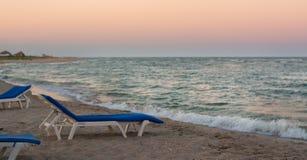 Sunbed op het strand tijdens zonsondergang Royalty-vrije Stock Foto's