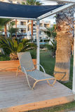 Sunbed in pavilion for relaxation on sea beach at sunset Stock Photos