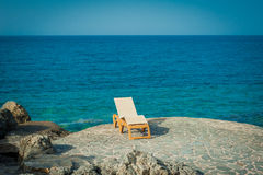 Sunbed on the rocks next to turquoise sea. Sunbed on the rocks next to sea Stock Photography