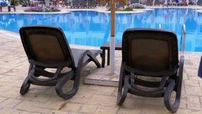 Sunbed-Ruhesessel nahe dem Swimmingpool mit blauem Wasser im Erholungsort von Ägypten stock video