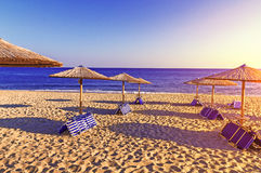 Sunbed, straw umbrella on beautiful beach background, burning su Stock Images