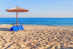 Sunbed, straw umbrella on beautiful beach background. Close Royalty Free Stock Images