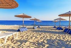 Sunbed, straw umbrella on beautiful beach background. Close Royalty Free Stock Photography