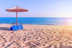 Sunbed, straw umbrella on beautiful beach. Close Stock Photos