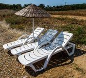Sunbed and Sun Umbrella. On sea coast in summer Stock Photos