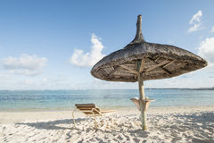 Sunbed and sunchair. Straw sunshade and a sunbed at a beautiful beach inviting to relax, Tourist concept for vacation and holiday, Mauritius, Africa Royalty Free Stock Photos