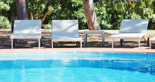 Sunbed and swimming pool Royalty Free Stock Photo