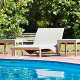 Sunbed and swimming pool Stock Images