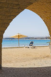 Sunbed on a tropical beach through archway Stock Photography