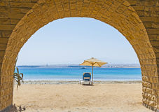 Sunbed on a tropical beach through archway Stock Images