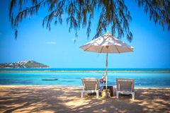 Sunbed and umbrella on a beautiful tropical beach Stock Photo