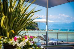 Sunbed and umbrella in Italian touristic resort. Over Garda Lake, Sirmione, Italy stock images