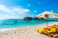 Sunbed and umbrella at Maldives island with white sandy beach an Stock Photo