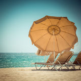 Sunbed and umbrella Stock Images