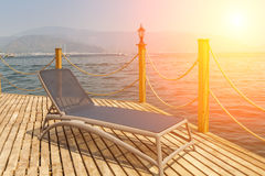 Sunbed on the wooden pier. On the background of mountains and the sea port Stock Photos