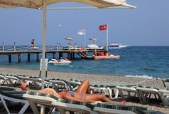 Sunbeds和伞在海滩胜地,女孩sunbath在懒人 库存照片