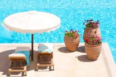Sunbeds和伞在水池附近 免版税库存图片