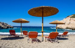 Sunbeds和阳伞在海滩希腊 免版税图库摄影