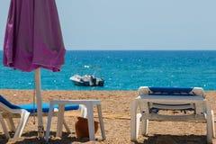 Sunbeds и большой зонтик на скалистом пляже, около океана Стоковое фото RF