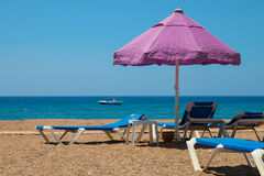 Sunbeds и большой зонтик на скалистом пляже, около океана Стоковая Фотография