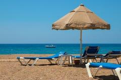 Sunbeds и большой зонтик на скалистом пляже, около океана Стоковое Изображение