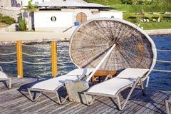 2 sunbeds и зонтика на деревянной пристани около моря Стоковые Фото