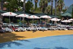 Sunbeds и зонтики на бассейне Стоковая Фотография