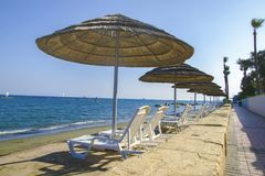 Sunbeds и зонтики на песчаном пляже Стоковые Фотографии RF