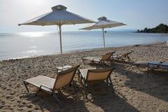Sunbeds и зонтики на песчаном пляже, Halkidiki, Греции Стоковая Фотография