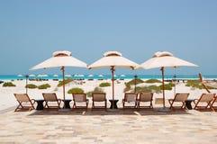 Sunbeds и зонтики на пляже Стоковое Изображение RF