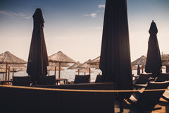 Sunbeds и зонтики на пляже около моря на заходе солнца Стоковое фото RF