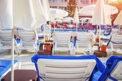 Sunbeds и зонтики около бассейна в тропическом курортном отеле Стоковая Фотография RF