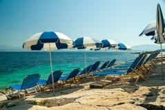 Sunbeds и зонтики (парасоли) на пляже в острове Корфу, Греции Стоковое фото RF