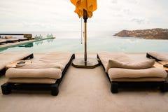 Sunbeds и зонтики рядом с бассейном Стоковое Фото
