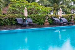 Sunbeds и парасоли на бассейне деревянной палубы близрасположенном Стоковое Изображение RF