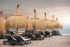 Sunbeds на песчаном пляже во время захода солнца - Playa de Torviscas, Тенерифе, Канарских островах Стоковое Фото