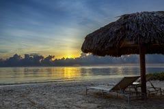 Sunbeds на пляже на восходе солнца Стоковое Фото