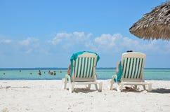 Sunbeds на пляже около моря Стоковые Фото