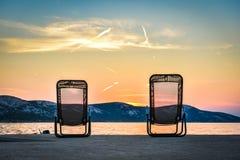 2 sunbeds перед заходом солнца на море Стоковые Изображения