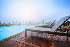 Sunbeds предводительствует около бассейна Стоковое Изображение RF
