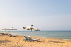 Sunbeds с зонтиками на красивом песчаном пляже Стоковые Изображения