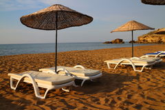 Sunbeds с зонтиками на пляже Стоковое Фото