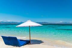Sunbeds с зонтиком на песчаном пляже около моря Стоковые Фотографии RF