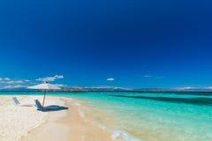 Sunbeds с зонтиком на песчаном пляже около моря Стоковое Фото