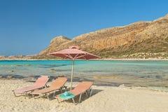 3 sunbeds, шляпа и зонтика на пляже Стоковая Фотография