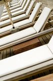 Sunbeds. A line of wooden sunbeds with white plastic covers Stock Photos