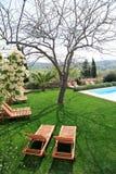 Sunbeds al lado de una piscina en jardín Fotografía de archivo libre de regalías