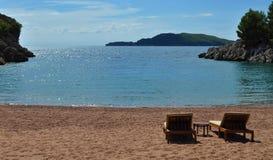 Sunbeds auf dem Sand vor dem Meer Lizenzfreies Stockbild