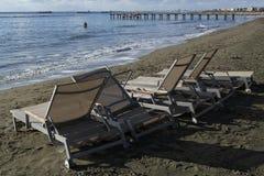Sunbeds auf dem Strand und einem Mann im Meer Stockfotos